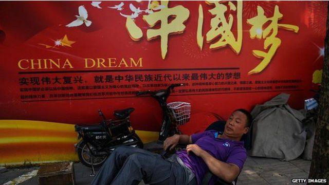 """男子躺卧在写着国家主席习近平喊出的""""中国梦""""的广告牌下,牌上写着""""实现伟大复兴,就是中华民族近代以来最伟大的梦想"""""""
