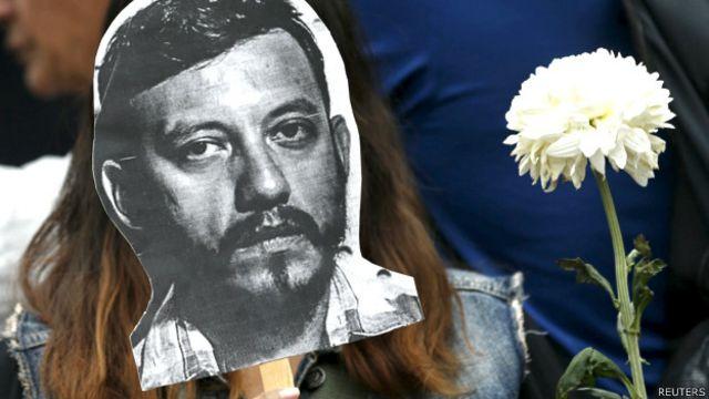Manifestante en México con una máscara que muestra el rostro del periodista asesinado Rubén Espinosa