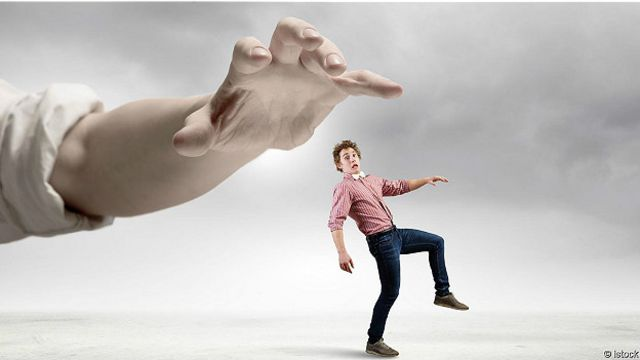 Огромная рука, занесенная над человечком