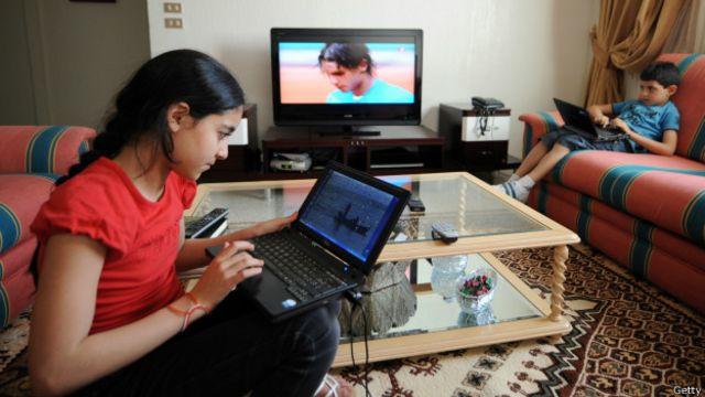 Niños viendo television y computadoras al mismo tiempo