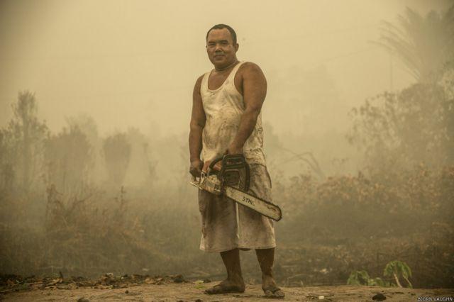 """""""Kami menemukan orang ini melakukan pekerjaan rutinnya di pinggiran kota Palangka Raya, dekat jembatan Tumbang Nusa, lokasi yang sangat terdampak kabut asap. Satu foto yang tidak bisa dilewatkan dan dia cukup senang diambil fotonya,"""" kata Bjorn."""