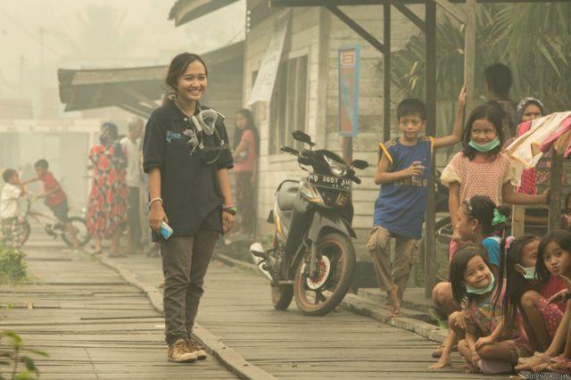 Emmanuela Dewi Shinta adalah aktivis lokal yang berdedikasi untuk mengedukasi bahaya menghirup asap beracun. Timnya datang ke daerah-daerah yang paling terkena dampak kabut asap, mendistribusikan air, makan siang, masker dan obat-obatan. Foto ini diambil di Desa Tumbang Nusa, ketika tim mereka membuka posko kesehatan yang sangat dibutuhkan.
