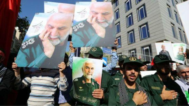 Unos militares iraníes llevan retratos del brigadier general iraní Hossein Hamedani, asesinado en el conflicto de Siria.