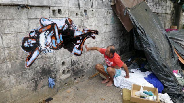 Osvaldo* admirado com a arte feita a partir da foto do casal (Crédito: http://www.theartfabric.com/)