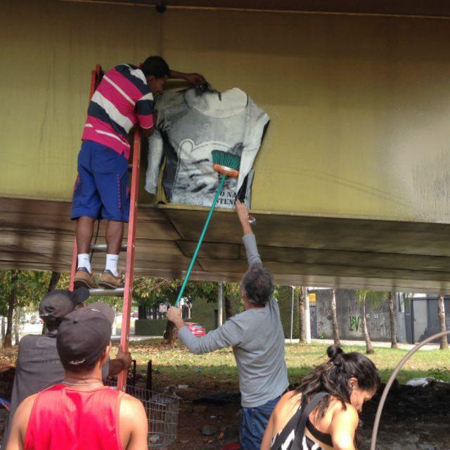 Os três 'irmãos de rua' se mobilizaram para conseguir uma escada e colar a arte do personagem fumando maconha