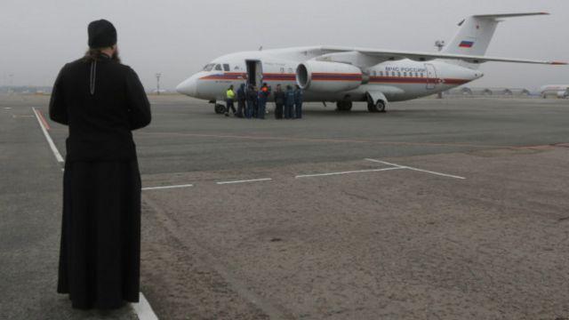 کشیش روس در فرودگاهی در سنپترزبورگ به استقبال هواپیمای حامل اجساد رفته است