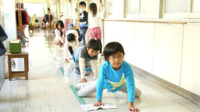 Niños escolares limpiando pisos en Japón