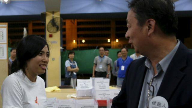 「青年新政」成員鄺葆賢(圖左)與競爭者資深區議員劉偉榮(圖右)握手。