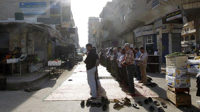 مردان در حال نماز در رقه. هنگام نماز همه مغازهها باید ببندند، ۵ آوریل ۲۰۱۴
