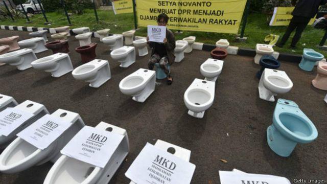Sejumlah pengunjuk rasa menyusun toilet di depan gedung DPR di Jakarta pada Kamis (03/12) kemarin sebagai simbol 'busuk dan kotor'.