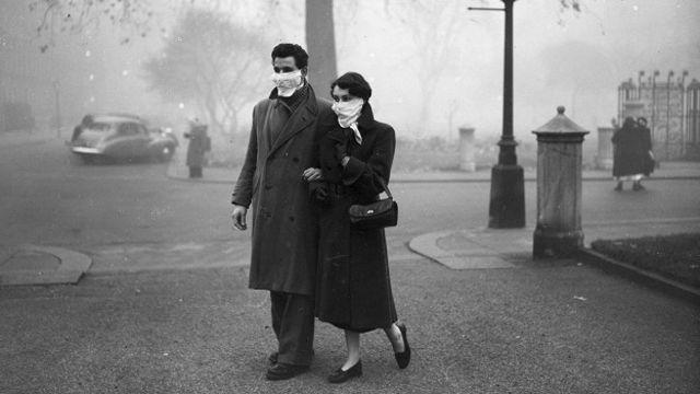 Пара на улицах Лондона, ноябрь 1953 года. Спустя почти год после Великого смога лондонцам все еще нужны были фильтрующие маски