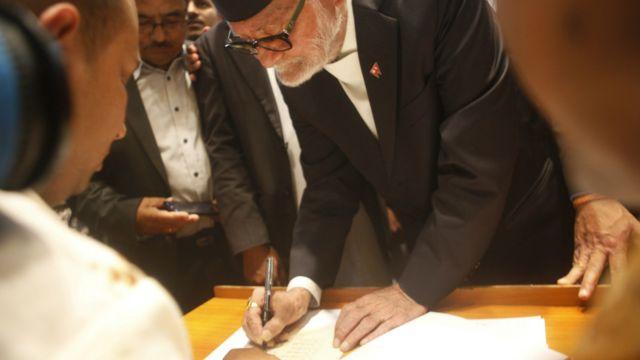 संविधान जारी गर्नुअघि असोज १, २०७२ मा संविधानसभा भवनमा तत्कालीन प्रधानमन्त्री सुशील कोइरालाका साथ अन्य सभासदहरुले हस्ताक्षर गरेका थिए। फाइल फोटो: एपी/ निरञ्जन श्रेष्ठ