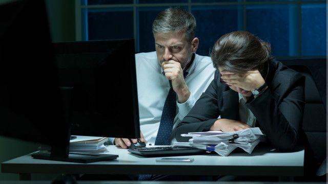 Dos personas estresadas frente a una computadora