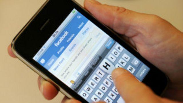 Imagen de Facebook en la pantalla de un teléfono celular en uso.