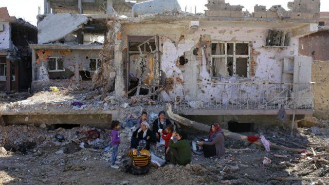 Aileler yıkılan evlerinin önünde bekliyor.