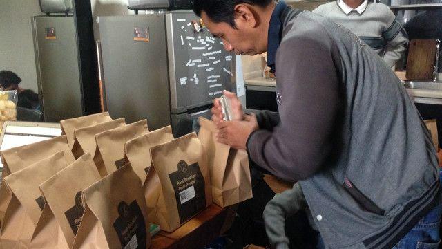 Kurir menyiapkan paket antaran katering pelanggan Kotak Sarapan.
