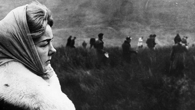 """No olvidar que para muchos, este tipo de crimen está lejos de ser fascinante: Ann Downey observando a la policía buscando el cuerpo de su hija Lesley, una de los cinco niños víctimas de los """"asesinos de los páramos"""", Ian Brady y Myra Hindley, en los años 60 en Reino Unido."""