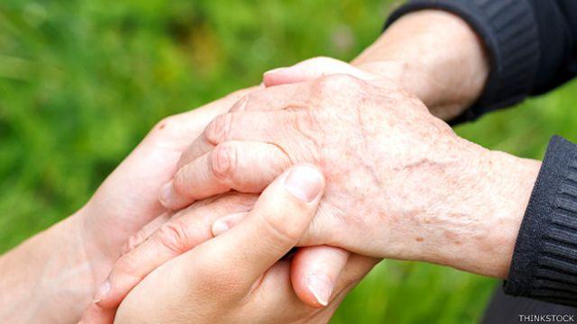 Una persona sosteniendo las manos de un familiar con la enfermedad de Parkinson