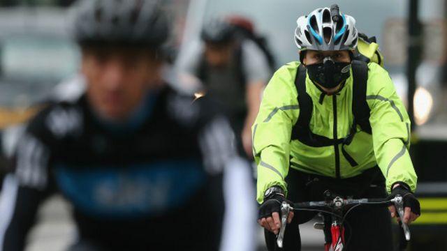 Женщина на велосипеде в маске