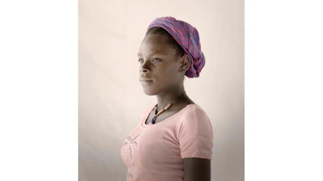 """على مدى السنوات الخمس الماضية تعيش إليان مع والدها واثنين من الأشقاء في مخيم للنازحين داخليا في أعقاب الزلزال الذي ضرب هايتي في عام 2010. أصبحت إليان حاملا من رفيقها واضطرت إلى ترك المدرسة. حينما كانت حاملا في شهرها السابع، أنجبت إليان طفلا توفي بعد فترة قصيرة من ولادته. تقول إليان """"كنت حاملا في الشهر السابع عندما شعرت بألم في الجزء الأسفل من البطن. وبعد أسبوع، قررت أن أذهب إلى المستشفى لمعرفة ما هي المشكلة. كل مستشفى ذهبت إليه رفض استقبالي وقالوا إن حالتي خطيرة جدا وأنني أو الطفل قد نموت أثناء الولادة""""."""