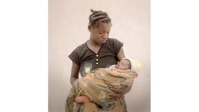 """مولينغا، 14 عاما، تعيش مع ابنتها ووالديها وزوجة والدها و10 أشقاء في قرية نائية في زامبيا. كانت مولينغا تذهب للمدرسة وكانت تريد أن تصبح طبيبة حتى اكتشفت والدتها أنها حامل. تقول مولينغا """"الأمومة صعبة. لم يعد لدي وقت للعب. كان يجب علي أن ألزم المنزل واعتني بابنتي وأغسل الحفاضات. قبل أن أنجب، اعتدت أن ألعب وأذهب إلى أي مكان أحبه. كنت أحب لعب كرة القدم""""."""