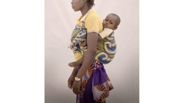 """آيسا، 15عاما، تعيش مع ابنتها فاتي، التي يبلغ عمرها 13 شهرا، وأمها وشقيقتين في منطقة ريفية في بوركينا فاسو. تعرضت آيسا لاعتداء جنسي على يد معلمها، وأصبحت حاملا نتيجة لذلك. أوقف المعلم عن العمل في وقت لاحق لمدة سنة واحدة. وتقول آيسا """"كان عمري 14 عاما حينما أصبحت حاملا. وكان ذلك بعد انتهاء امتحان المرحلة الابتدائية. اتصلت بمعلمي لمعرفة النتيجة. ومنذ أن حصل على رقم هاتفي، استمر في الاتصال بي وطلب مني مقابلته في منزله. قلت له إنني لن أذهب إليه. لكنه في يوم ما، هددني وقال لي إنه إذا لم أذهب إليه، فستكون هناك مشكلة. شعرت بالخوف وذهبت إلى هناك للحصول على نتائج امتحاني، ثم اغتصبني""""."""