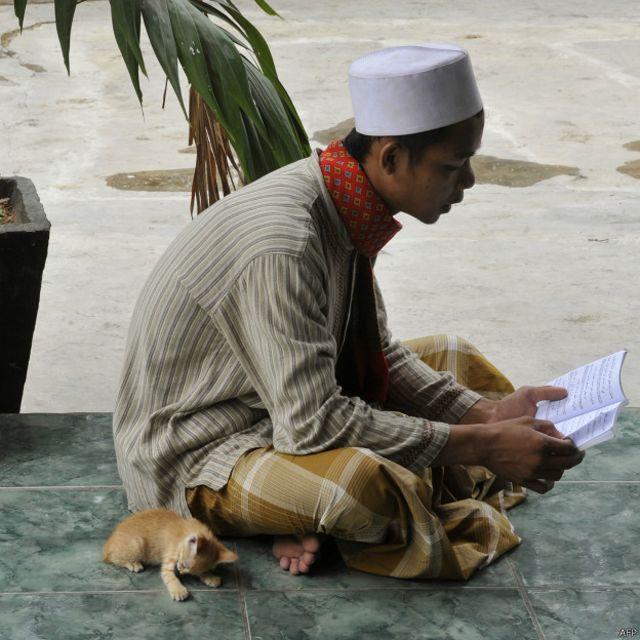 Seorang muslim tengah membaca sebuah kitab di komplek makam Habib Hasan bin Muhammad al Hadad di Jakarta, 16 April 2010. Praktik ziarah kubur ditolak oleh gerakan Wahabi karena dianggap menyalahi ajaran Islam.