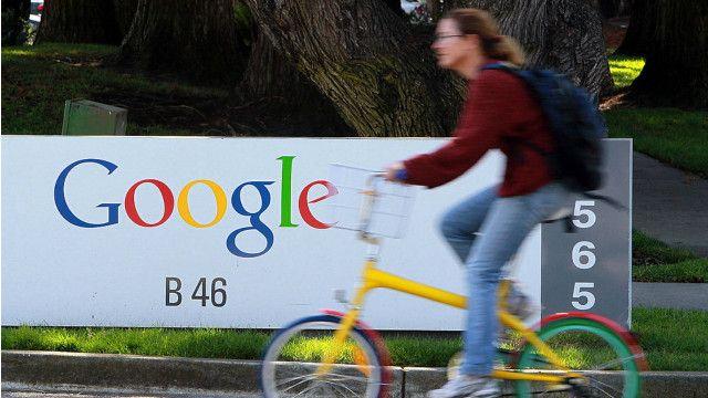 Una persona en una bicicleta frente al logotipo de Google