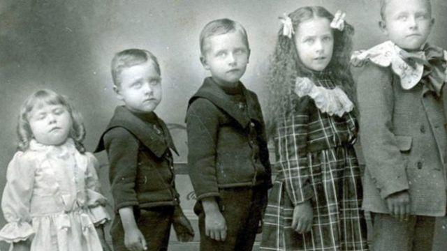 Fotografía de varios niños con una hermanita muerta.