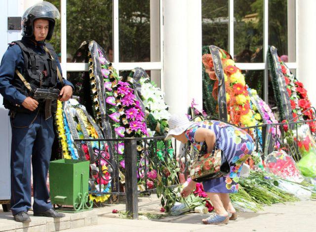 در مغازههای فروش اسلحه که مورد حمله افراد مسلح قرار گرفت دسته های گل گذاشت شده است