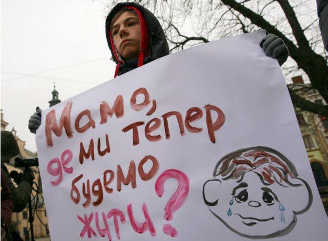 Хлопчик-переселенець тримає плакат на акції переселенців