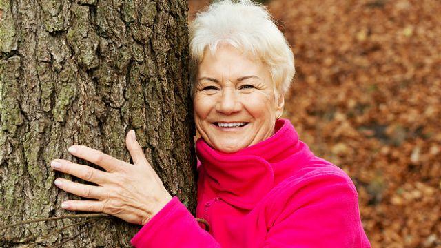 Пожилая женщина обнимает дерево