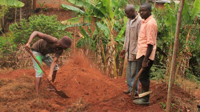 Après le premier coup de pioche donné par un notable, des membres de la famille se mettent à exhumer le crâne du défunt.