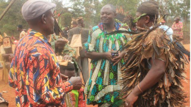 Les chefs des groupes de danse se concertent sur l'ordre de passage de leurs troupes pour la cérémonie funéraire.