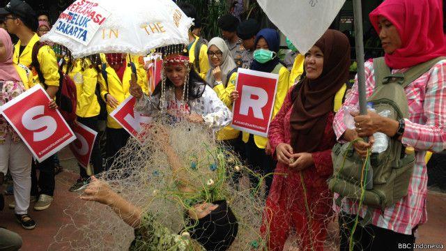 Para aktivis, nelayan dan mahasiswa menggelar happening art dalam unjuk rasa di depan Kemenko Kemaritiman.
