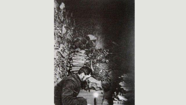 """بول بيليو، الخبير الفرنسي بعلم الصينيات يقرأ مخطوطات في """"مكتبة الكهف"""" بمدينة دونهوانغ سنة 1908"""