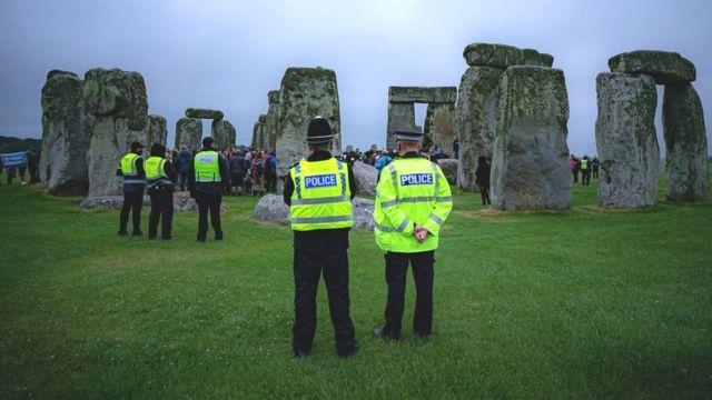 Police watch crowds celebrate during Summer Solstice at Stonehenge, where some people jumped over the fence to enter the stone-circle to watch the sun rise at dawn of the longest day in the UK. The stones have been officially closed for the celebrations, which see huge crowds inside the circle, due to the coronavirus lockdown extension.