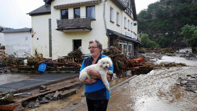 Un hombre carga a un perro a través de los escombros traídos por el agua.