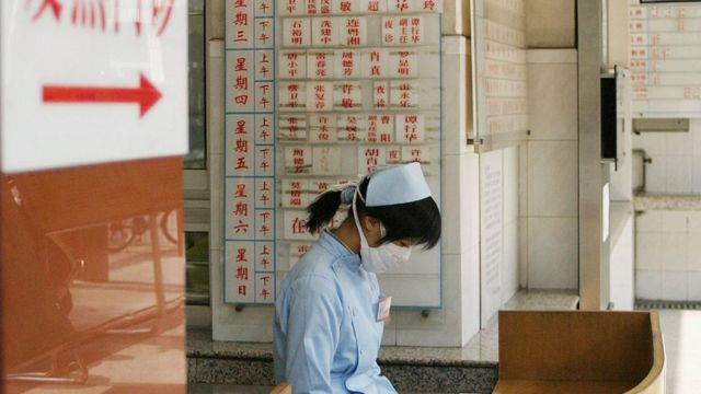 A nurse wears a face mask to protect against Severe Acute Respiratory Syndrome (SARS), 2004