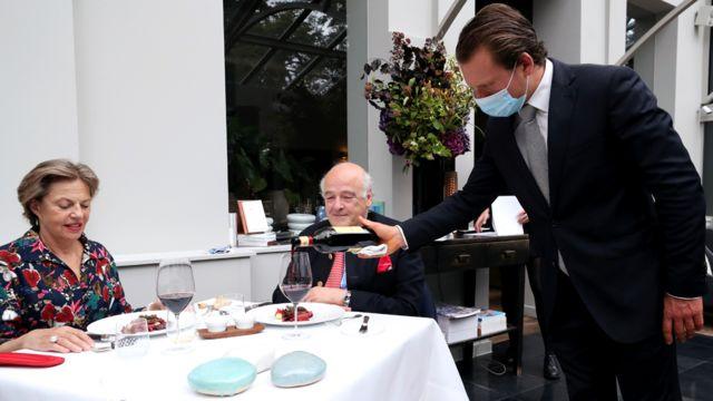 Garçom serve clientes em restaurante na Bélgica