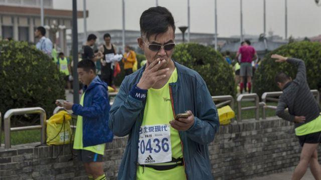 北京マラソンの開始前にたばこを吸うランナー(9月20日)