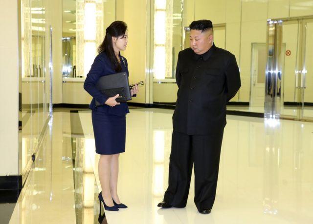 (캡션) 리설주 여사가 김정은 위원장의 서류 가방과 안경으로 보이는 것을 들고 있다