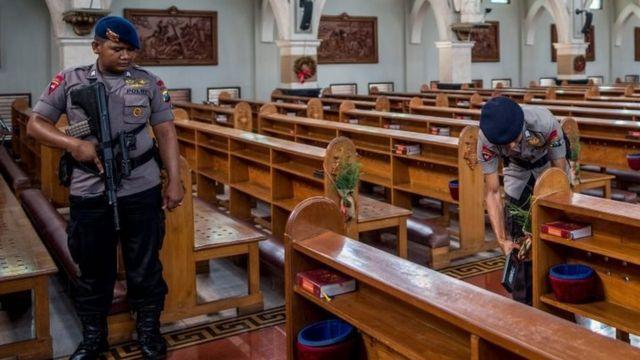 Polisi memeriksa gereja di Surabaya pada malam Natal.