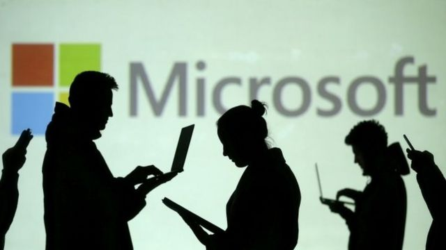 Silhouettes of people using electronics in front of Microsoft logo
