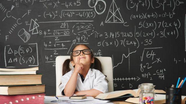 Imagem mostra menina sentada em frente a quadro negro repleto de números e cálculos