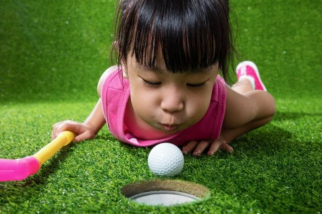A little girl, lying on a mini-golf grass floor, blowing the ball into a hole