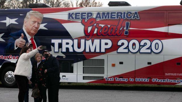 مؤيدون يلتقطون صورة سيلفي مع حافلة تحمل علامة ترامب في ولاية جورجيا