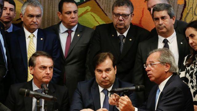 Bolsonaro, Maia e Guedes aparecem sentados em mesa e observados por outras pessoas durante apresentação da proposta da reforma da Previdência para militares