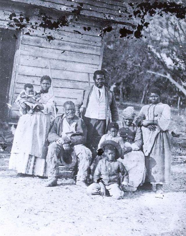 Fotografia de família de escravos nos Estados Unidos - mulher com criança no colo, senhor sentado, homem adulto em pé, duas mulheres e duas crianças