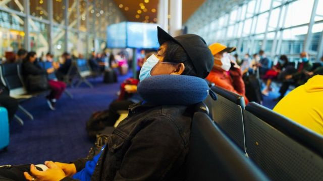Ciudadanos esperando vuelo en aeropuerto.
